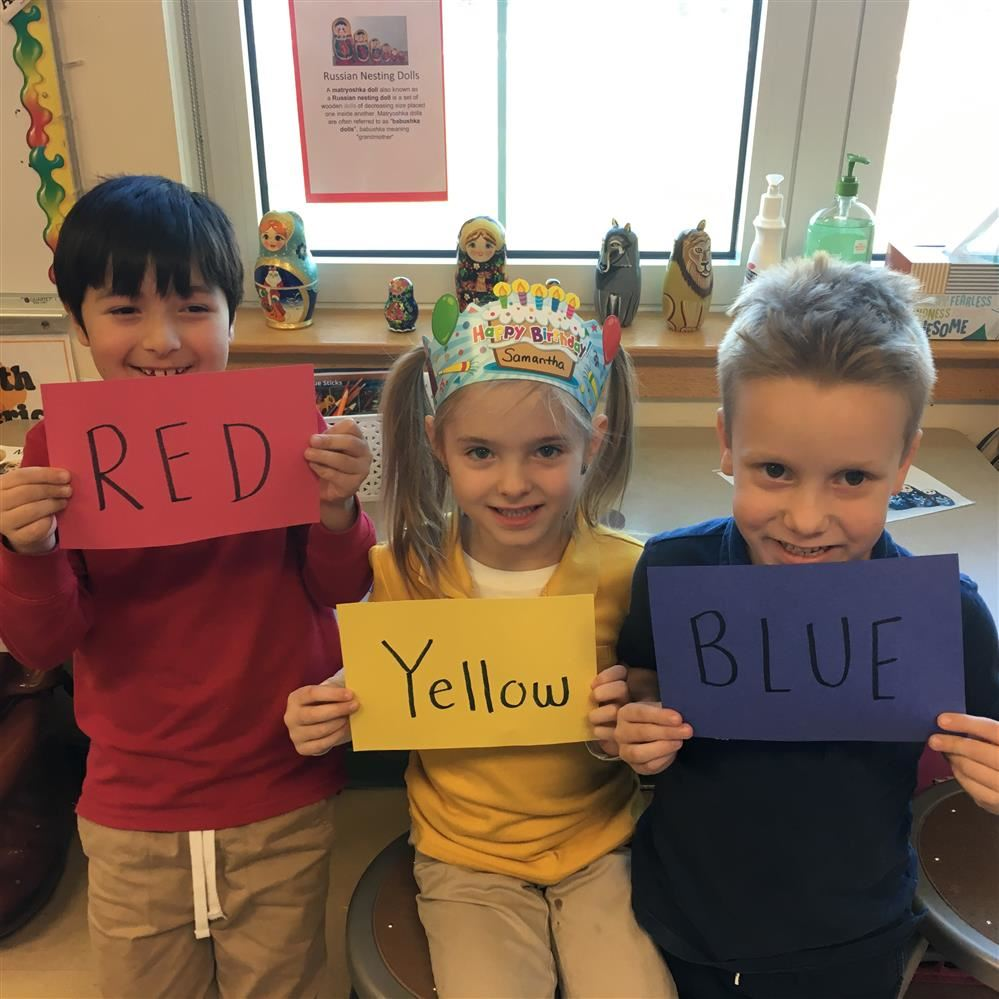 students holding red, yellow, blue signs