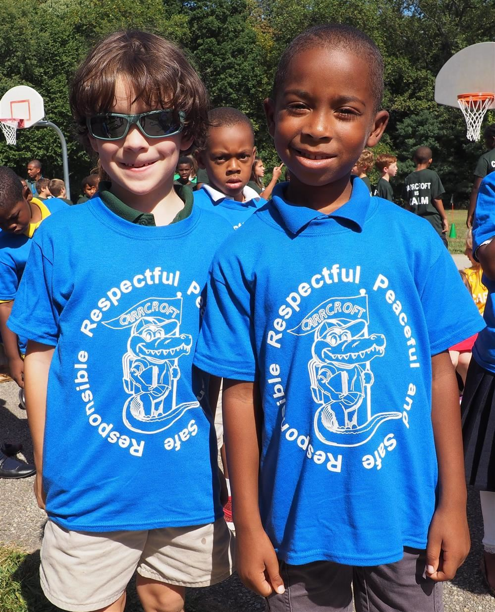 two kids standing together in blue tshirts