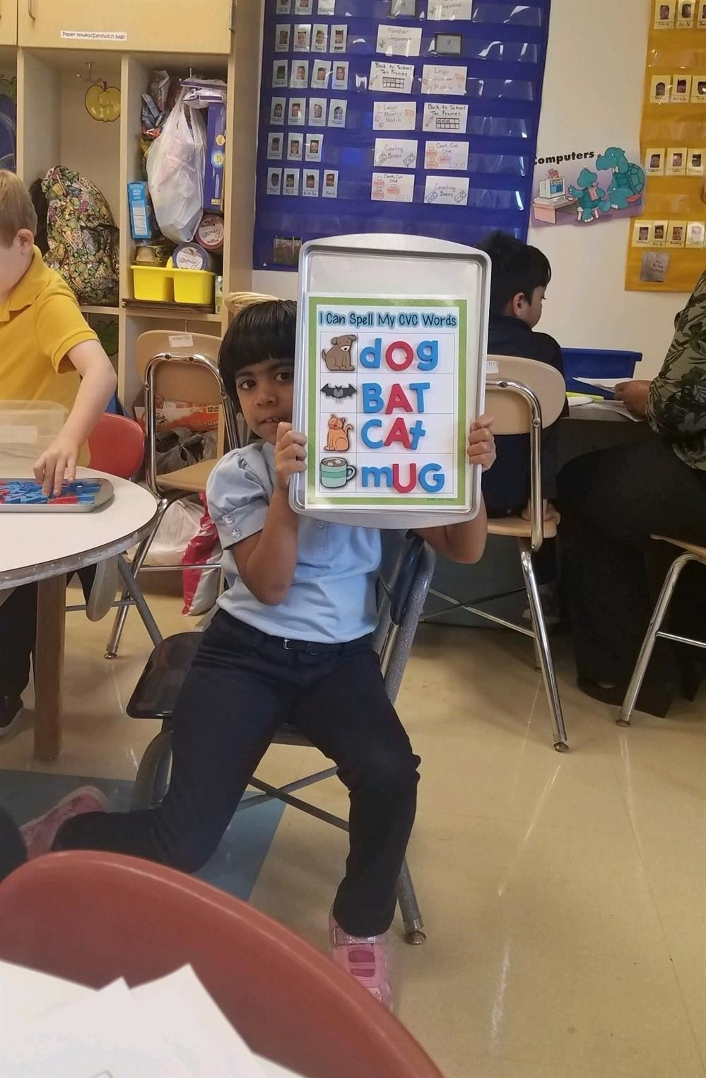 student holding up spelling words